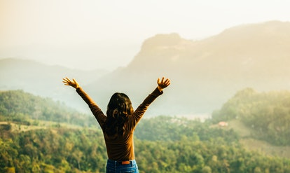 Girl thank for giving.raised hands at mountains.Travel with nature landscape