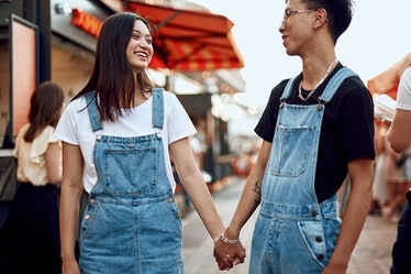 Love and date concept. Young happy asian man and woman walking together around city holding hands