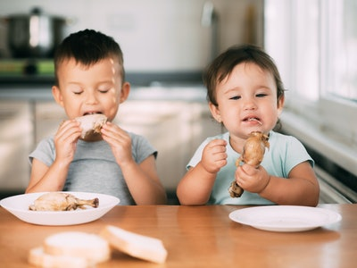 Kids boy and girl , brother and sister in the kitchen having fun and eating chicken with appetite is very cute