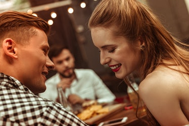 Flirting couple. Close-up face portrait of beautiful attractive young-adult cheerful joyful couple f...