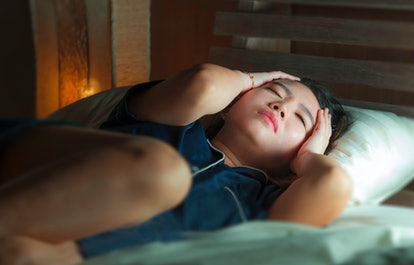 home dramatic lifestyle portrait of young beautiful sad and depressed Asian Chinese woman awake in bed late night suffering anxiety crisis and depression problem feeling desperate