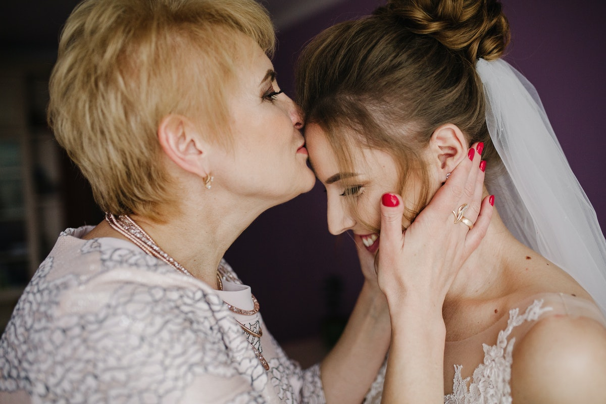 Bride on wedding day holding her mother's hands. Mother of the bride blesses the bride for a happy family life.
