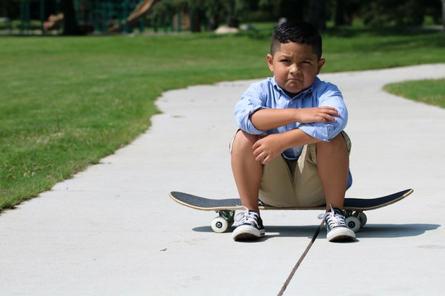 A young hispanic child is sitting on a skateboard in a park, upset or angry.