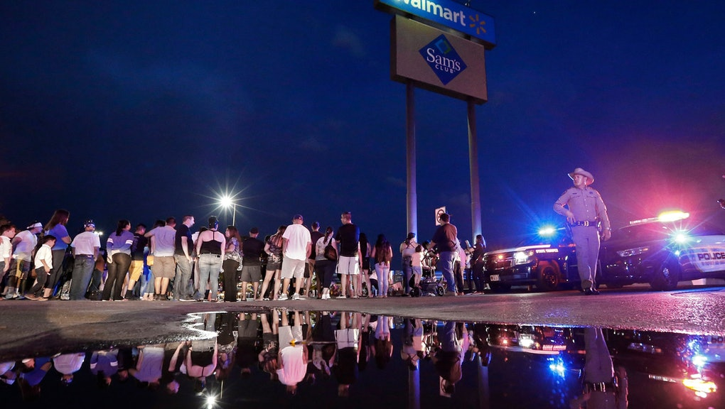 A State Trooper walks past a water puddle while people stand around the make shift memorial at the s...