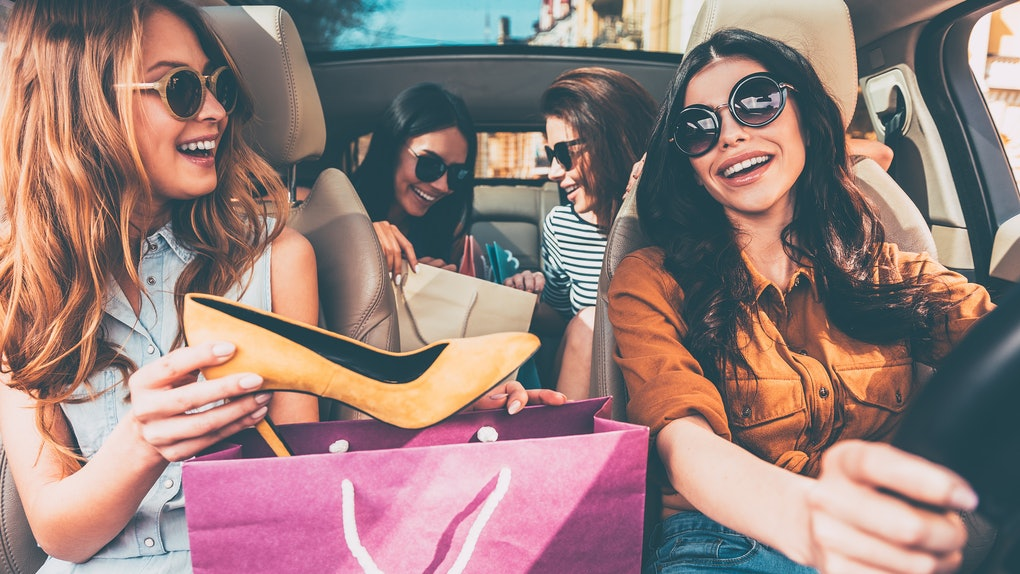 Next stop is lingerie shop! Four beautiful young cheerful women holding shopping bags and looking at each other with smile while sitting in car