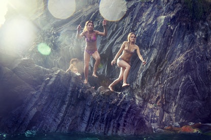 two young women diving from a cliff in the sea. Concept of beautiful people having fun in summertime