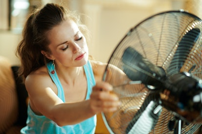 unhappy young housewife in the modern living room in sunny hot summer day enjoying freshness in the front of fan suffering from summer heat.