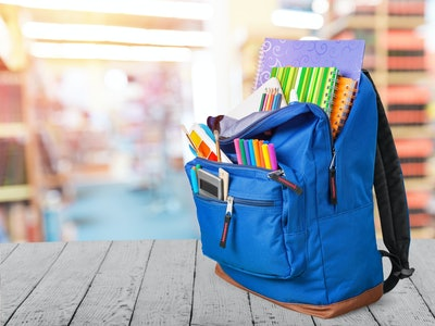 Open blue school backpack on withe table in library background.