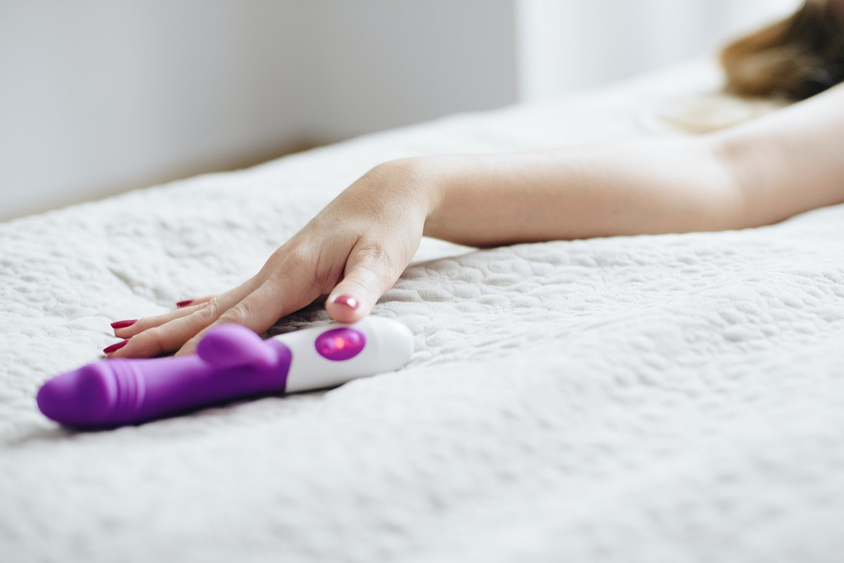 Young woman's hand reaching for sex toy dildo in bed