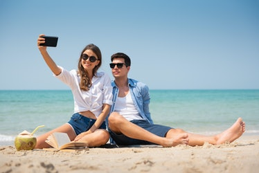 Smiling Young couple in casual clothes and sunglasses taking a selfie on the beach with copy space.