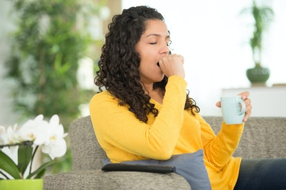 sleepy woman holding hot drink on knee on sofa