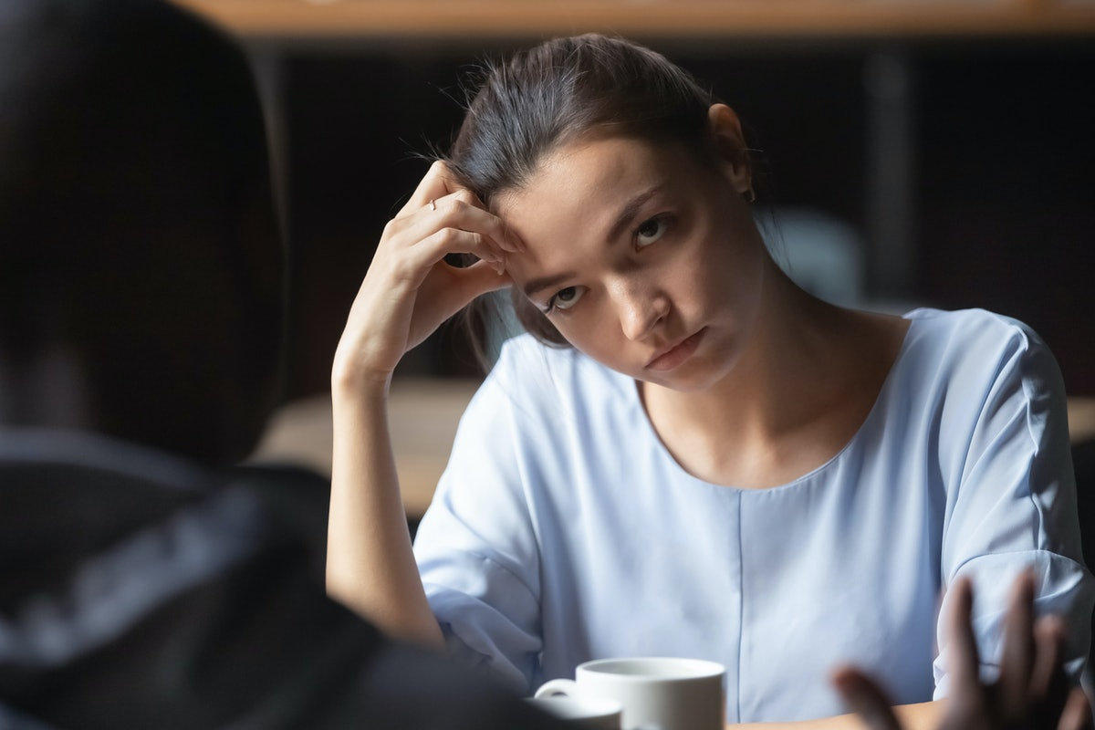 Bored unhappy girlfriend listening to African American boyfriend in cafe, bad first impression and d...