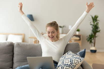 Excited smiling woman celebrating online win, victory, look at screen, using laptop at home, sitting on comfortable sofa, screaming with raising hands, receiving email with good news, new opportunity