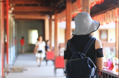 A teenage girl wearing a travel bag, a travel bag on a holiday. At a place decorated in Chinese style.
