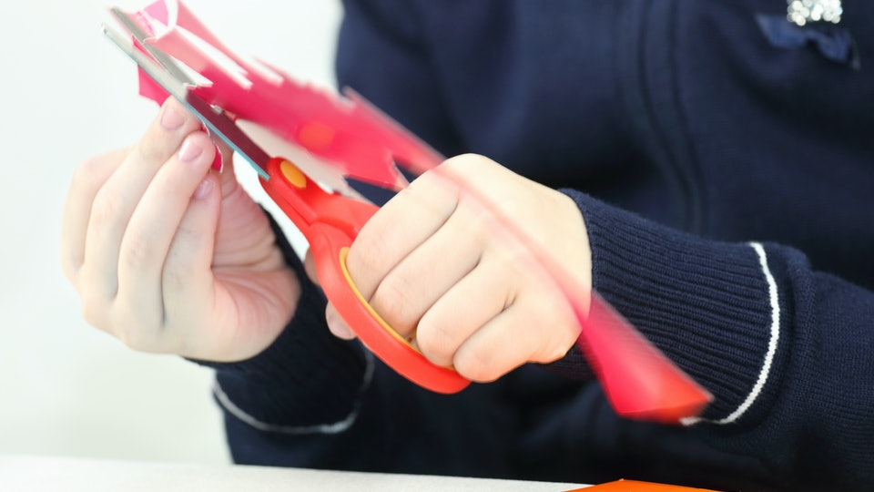 Hands of girl cutting flower from red paper for crafts, close up