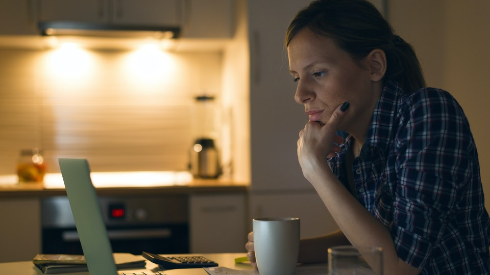 Serious woman thinking while reading an e-mail on laptop at home