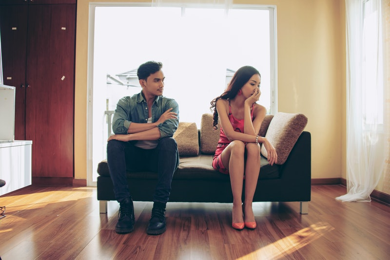 Unhappy couple sitting on couch after quarrel fight thinking of break up or divorce, black upset man...