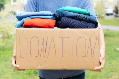 Man holding a Donate Box with clothes, donation and charity concept