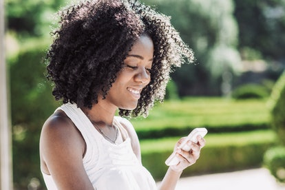 Smiling pretty young black woman texting on smartphone in park. Communication concept. Side closeup view.