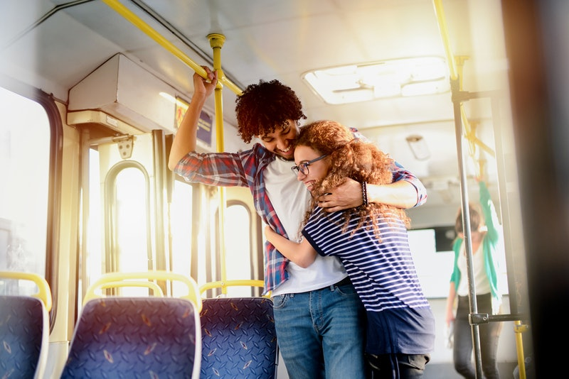 Cute young couple hugging in a public transport. Having fun and traveling together.