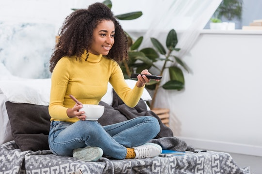 attractive stylish african american girl holding bowl with food and watching tv at home