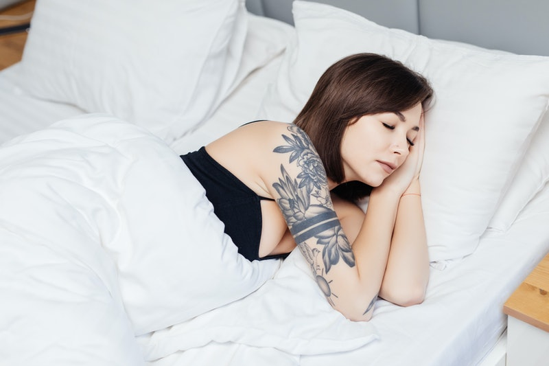 Beautiful young woman sleeping in a white bed.