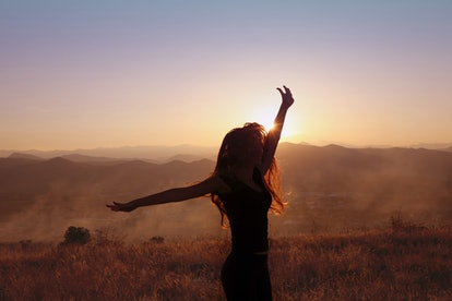 Sunset mountain. Free woman outstretched arms with blowing hair running in wheat field enjoying life.