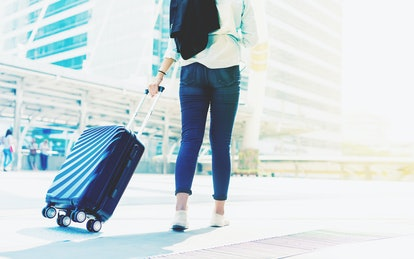 Beautiful young tourist girl with travel bag or suitcase walking at terminal walkway for travel abroad in international airport,Concept of lonely travelator lifestyle