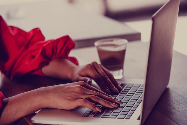 Women working on laptop computer fingers macro