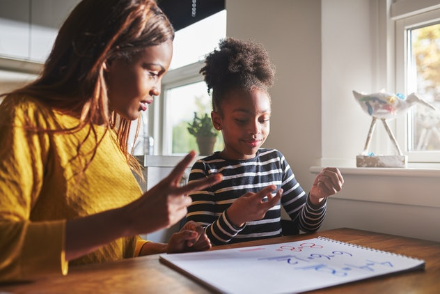 Patient mom teaching daughter schoolwork at home, black family