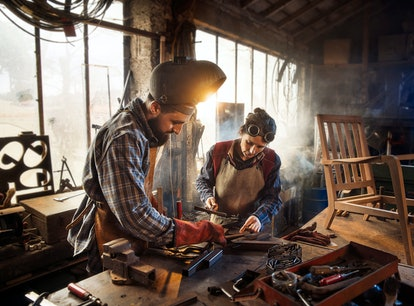 Two artisans welder in their craft workshop welding metal parts to assemble them on a designer woode...
