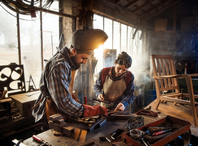 Two artisans welder in their craft workshop welding metal parts to assemble them on a designer wooden armchair. A man and a woman