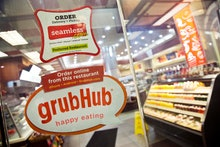 GrubHub, Seamless Signs for GrubHub and Seamless are displayed on the door to a New York restaurant,...
