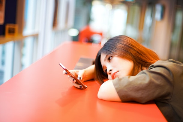 Lonely sad girl lying down on the table waiting for text message from phone