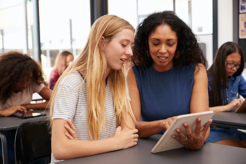 Teacher helps blonde teenage schoolgirl with tablet computer