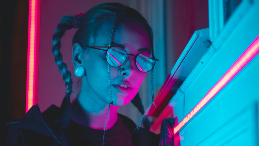Young pretty girl with unusual hairstyle near glowing pink and blue neon lights of the city at night. Dyed blue hair in braids. Serious hipster teenager in glasses and beautiful lenses.