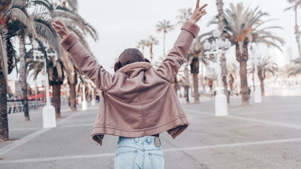 Back view of a young female wanderer out sightseeing in a foreign city during weekend,trendy woman traveler in pink jacket and jeans walking on unfamiliar street, spring adventure in Los Angeles