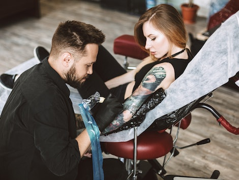 Professional tattooer doing tattoo on hand by tattoo machine while girl thoughtfully watching process in modern studio