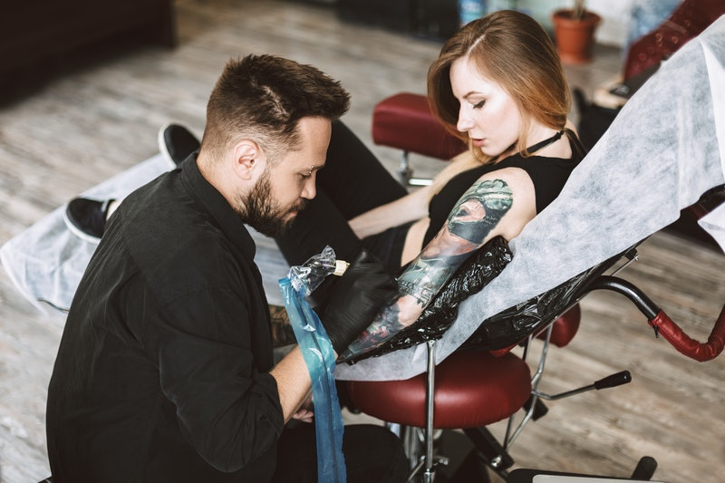 Professional tattooer doing tattoo on hand by tattoo machine while girl thoughtfully watching proces...