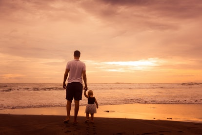 Father and little daughter standing on beach at sunset. Dad and baby girl near sea
