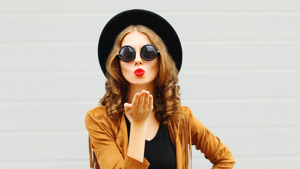 Portrait pretty woman sends air sweet kiss wearing a black hat, sunglasses and brown jacket outdoors over urban grey background