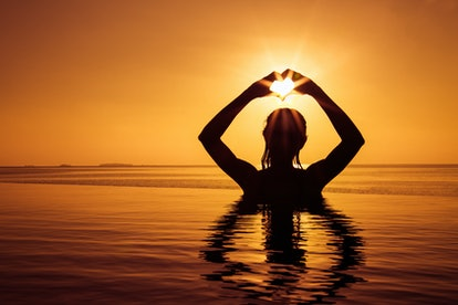 Silhouette of beautiful girls make a heart with her hands in the infinity pool. Maldives.