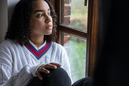 Beautiful mixed race biracial African American girl teenager female young woman sad depressed or thoughtful looking out of a window