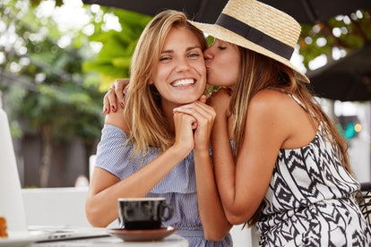 Lovely woman with cheerful expression happy to recieve kiss from her girlfriend, sit together at coffee shop, use modern laptop for online communication, demonstrate devoted love to each other