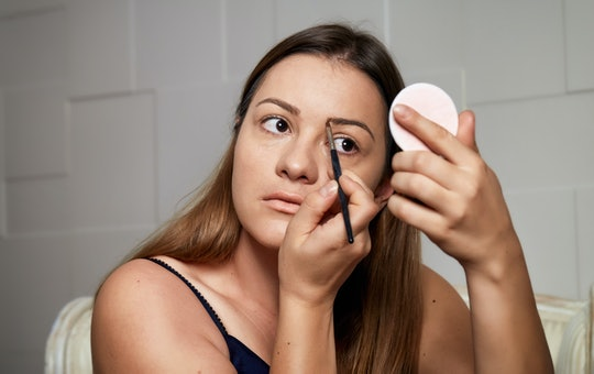 Young woman applying eyebrows make-up. Beautiful woman applying eyeshadow on her eyebrow with brush. Dermatology, facial treatment, skin care and anti-aging mask.