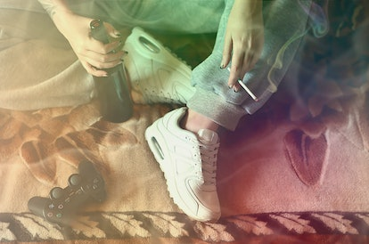 A girl sitting on the couch, smoking a cigarette, drinking beer and playing on a game console in a s...