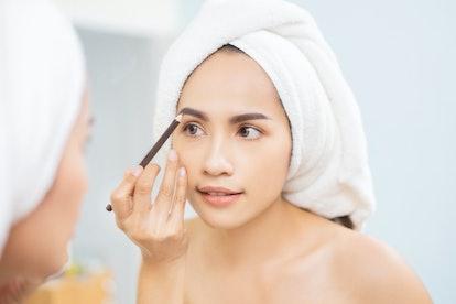 Beautiful Woman asian doing Makeup Eyebrow Pencil