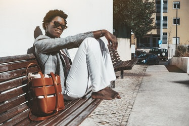 A young charming fancy African female in a plaid jacket and white trousers is sitting barefoot on a ...