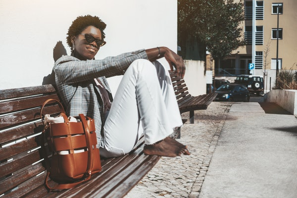 A young charming fancy African female in a plaid jacket and white trousers is sitting barefoot on a wooden street bench and enjoying the bright sun, with a copy space place on the right for your text