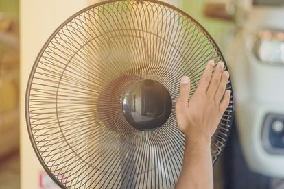 Hand of Young man touch and adjust  on front grills of electric fan for a good wind in his home in summer of april in Thailand.